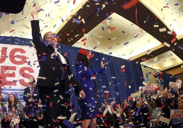 Confetti falls as Democrat Doug Jones and his wife Louise wave to supporters Tuesday, Dec. 12, 2017, in Birmingham, Ala. (AP Photo/John Bazemore)