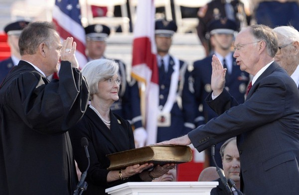 Alabama Chief Justice Roy Moore administers the oath of office to Alabama Gov. Robert Bentley. A year later, both are in hot water.