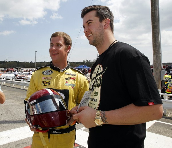 """Quarterback AJ McCarron (right) and driver Thomas """"Moose"""" Praytor display an autographed racing helmet bearing the Alabama Crimson Tide's logo before the ARCA Mobile 200 on March 22, 2014, at Mobile International Speedway in Irvington, Ala. The helmet was auctioned for charity."""