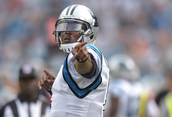 ff8a89222df Carolina Panthers quarterback Cam Newton signals for a first down after  scrambling for a gain during