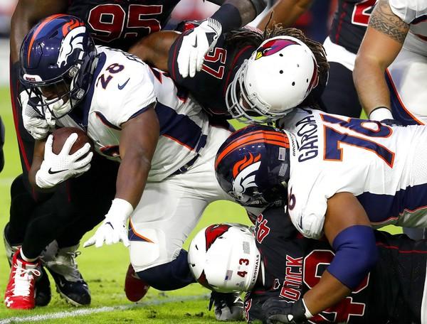 Arizona Cardinals middle linebacker Josh Bynes (57) tackles Denver Broncos running back Royce Freeman during an NFL game on Thursday, Oct. 18, 2018, in Glendale, Ariz.