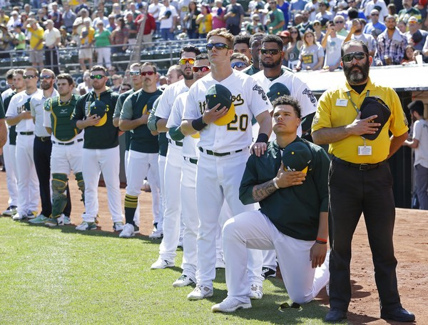 Oakland Athletics catcher Bruce Maxwell takes a knee during the national anthem before an American League game against the Texas Rangers on Sept. 24, 2017, in Oakland, Calif.