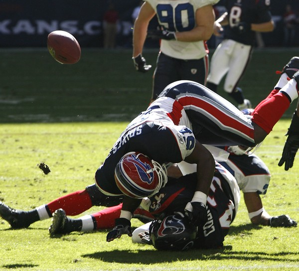 Buffalo Bills linebacker Takeo Spikes causes Houston Texans running back Jameel Cook to fumble during an NFL game on Nov. 19, 2006, in Houston.