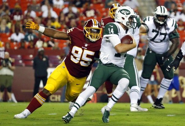 Washington Redskins defensive tackle Da'Ron Payne closes in on New York Jets quarterback San Darnold during an NFL preseason game on Thursday, Aug. 16, 2018, in Landover, Md.