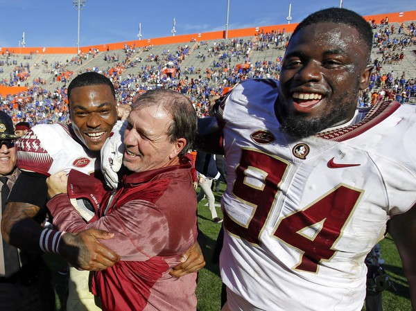 Florida State defensive back Derwin James, left, and defensive tackle Walvenski Aime (94) celebrate with Florida State head coach Jimbo Fisher, center, after defeating Florida 38-22 in an NCAA college football game, Saturday, Nov. 25, 2017, in Gainesville, Fla. Florida State won 38-22.