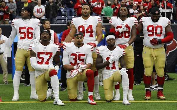 San Francisco 49ers players Eli Harold (57), Eric Reid (35) and Marquise Goodwin (11) kneel during the national anthem before an NFL game against the Houston Texans on Sunday, Dec. 10, 2017, in Houston.