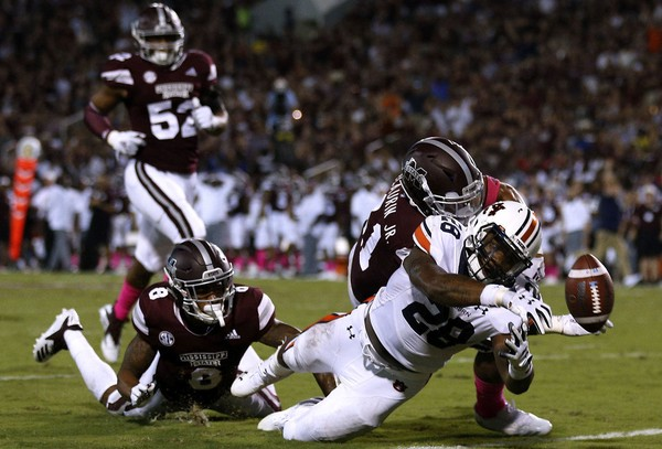 aTarvious Whitlow of the Auburn Tigers fumbles the ball as Mark McLaurin and Maurice Smitherman of the Mississippi State Bulldogs defend during the second half at Davis Wade Stadium on October 6, 2018 in Starkville, Mississippi.