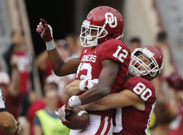 Oklahoma tight end Grant Calcaterra (80) celebrates with teammate wide receiver A.D. Miller (12) following Miller's touchdown in the second half of an NCAA college football game against UCLA in Norman, Okla., Saturday, Sept. 8, 2018. Oklahoma won 49-21. (AP Photo/Sue Ogrocki)
