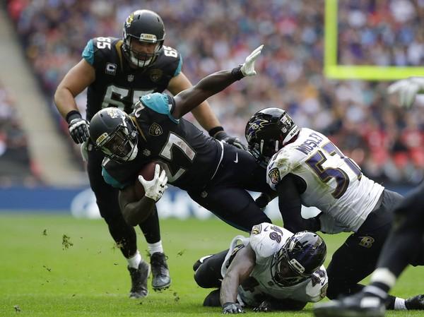 Baltimore Ravens middle linebacker C.J. Mosley tackles Jacksonville Jaguars running back Leonard Fournette during an NFL game at Wembley Stadium in London on Sept. 24, 2017.