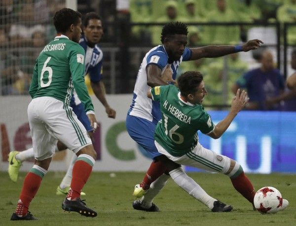 Mexico faces United States in a World Cup qualifier. Mexico's Miguel Herrera, right is taken down by a Honduras players and Mexico's Jonathan Dos Santos, left, looks on during a 2018 Russia World Cup qualifying soccer match between Mexico and Honduras at Azteca Stadium in Mexico City, Thursday, June 8, 2017. Mexico won the match 3-0.(AP Photo/Eduardo Verdugo)