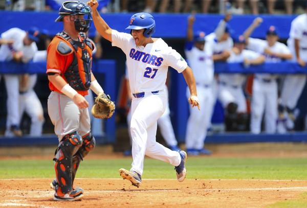 Florida infielder Nelson Maldonado scores a run off a base hit by teammate Wil Dalton during the third inning of an NCAA Super Regional college baseball game against Auburn, Saturday, June 9, 2018, in Gainesville, Fla. Florida defeated Auburn 8-2. (AP Photo/Matt Stamey)