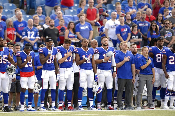Buffalo Bills players and staff stand during the performance of the national anthem before an NFL preseason game against the Carolina Panthers on Thursday, Aug. 9, 2018, in Orchard Park, N.Y.
