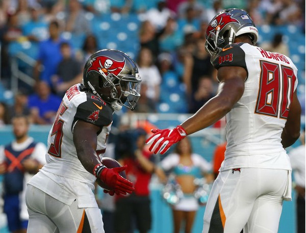 Tampa Bay Buccaneers running back Peyton Barber (left) receives congratulations from tight end O.J. Howard after scoring a touchdown against the Miami Dolphins during an NFL preseason game on Thursday, Aug. 9, 2018, at Hard Rock Stadium in Miami Gardens, Fla.