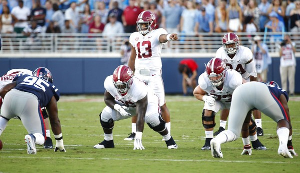 Alabama quarterback Tua Tagovailoa (13) readies to start the play behind the block of offensive lineman Lester Cotton Sr., (66), center during the first half of their NCAA college football game against Mississippi on Saturday, Sept. 15, 2018, in Oxford, Miss. Alabama won 62-7.(AP Photo/Rogelio V. Solis)