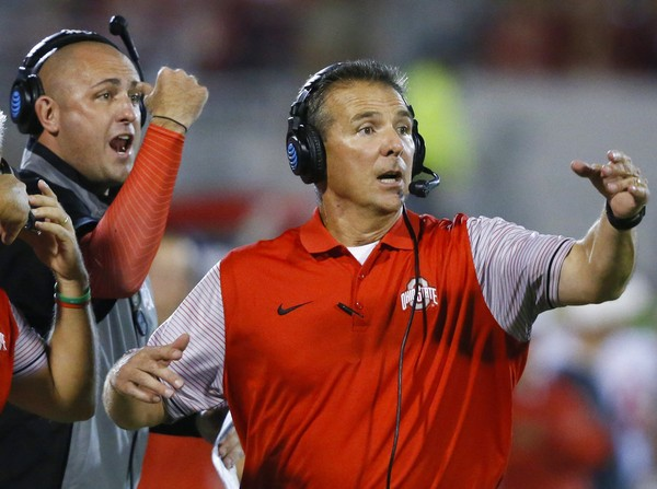 In this Sept. 17, 2016, Ohio State head coach Urban Meyer, right, and then-assistant coach Zach Smith, left, gesture from the sidelines during an NCAA college football game against Oklahoma in Norman, Okla. Ohio State expects to open fall camp as scheduled on Friday, Aug. 3, 2018, but without coach Urban Meyer. Meyer was put on administrative leave on Wednesday, Aug. 1 over the handling of a longtime assistant who has been accused of domestic violence. Co-offensive coordinator Ryan Day will be running the team while Ohio State investigates claims that Meyer's wife knew about 2015 allegations of abuse against former Buckeyes assistant Zach Smith, who was fired last week. (AP Photo/Sue Ogrocki, File)