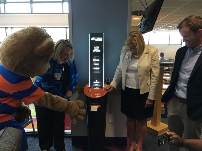 Paws, the library lion cub, Library Director Pam Hickson-Stevenson, Children's Hospital President Grace Wakulchik and Knight Akron Program Director Kyle Kutuchief await a short story from the new dispenser.