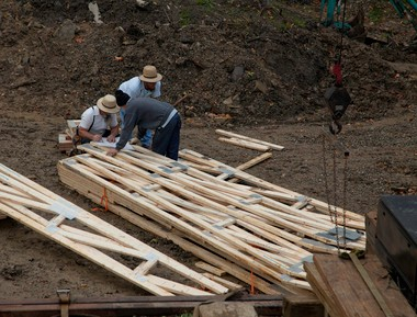 Amish workmen sort through lumber intended for ceiling joists in the Butler-Nissen house during its construction.