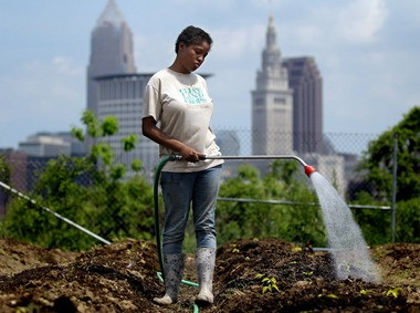 Alesiah Berry, 22, waters tomatoes for the Cleveland Crops garden in Ohio City in May. The Next City Vanguard conference in Cleveland included a visit to the farm.