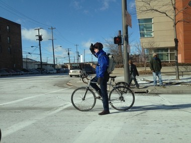 Jacob VanSickle shades his eyes from bright sun on a chilly day while waiting for a light to change on Superior Avenue.