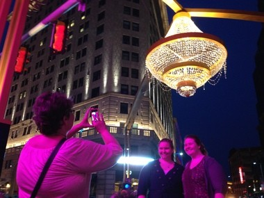 Cheryl Dwyer of Bristol, Vt., snaps a photo of the new Playhouse Square chandelier and of her daughter, Erin Dunn, left, and friend, Jane Hudson.