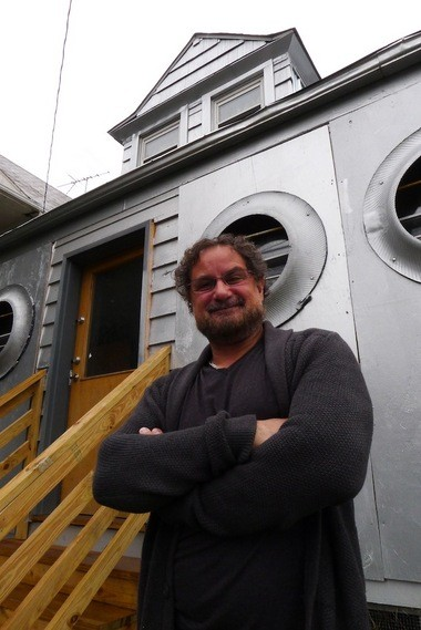 Loren Naji in front of his silver-painted Satellite Gallery, which will open Friday. The windows of the house in which the gallery operates has been augmented with truck tire sidewalls to create a porthole effect.