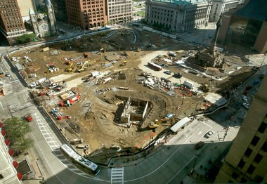 An overlook view of Public Square on Monday, July 13 shows the curved outline of a bench and peripheral promenade taking shape at the northeast corner of the 6-acre civic space, plus the rectangular form of an underground service vault for a water feature, at the southwest corner of the square, closest to the photo's viewpoint.