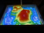 A computer and projector provide the bright colors and topographical images in the augmented reality sandbox.