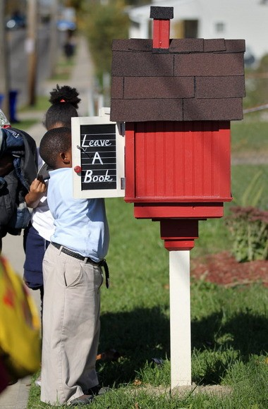 A student goes up to the Little Free Library at Miles Park School to select a book to take home.