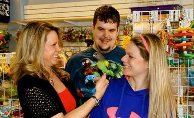 Make-a-Wish Volunteers Karan Ankney and Crystal Ankney (left to right) partner with In a Pickle Parrot Shop Owner Paul Palisin to make a dream of a pet parrot come true for a seriously ill child.