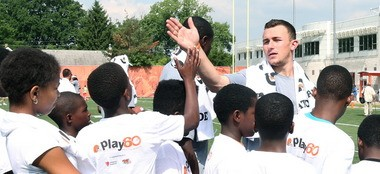 Browns rookie quarterback Johnny Manziel, giving high fives to a line of youngsters at the 2014 NFL Rookie Symposium PLAY 60 Youth Football Clinic.