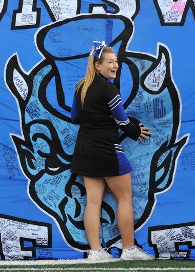 Kristen Horton, 17, the Brunswick High School cheerleader captain, holds the Blue Devil banner before the Sept. 20 at Judy Kirsch Field in Brunswick.