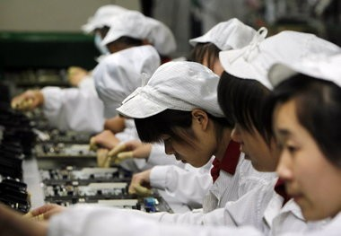 Staff members work on the production line at the Foxconn complex in the southern Chinese city of Shenzhen, Southern city in China. Foxconn makes iPhones and other electronics that get imported to the United States, but experts say the benefits of offshoring such work are shrinking.