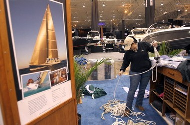 Christine Corbissero, director of customer service at Fairport Harbor-based Tartan and C&C Yachts, preps the company's display at the Cleveland Mid-America Boat Show that opened Thursday and runs through Monday at the I-X Center
