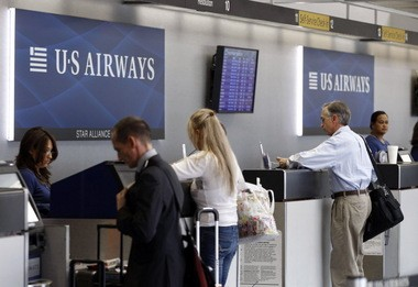 US Airways employees assist customers at a ticket counter at the Charlotte/Douglas International airport in Charlotte, N.C.