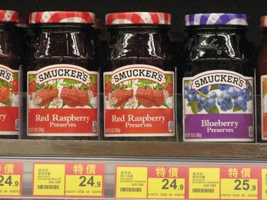 Jars of J.M. Smucker's red raspberry preserves line a shelf at the Wellcome grocery store in Hong Kong, with prices listed in Hong Kong dollars. The Smucker company said its sales of international, foodservice and natural foods rose 28 percent in its third quarter of fiscal 2013, to $350.6 million.