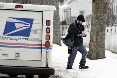 "U.S. Postal Service carrier Brandon Liverman delivers mail on Feb. 7 in Indiana. As the Postal Service tries to cut spending and raise cash, the agency has licensed trademarks and the brand ""Rain, Heat & Snow"" to a Cleveland apparel company, which is planning a line of clothing and accessories."