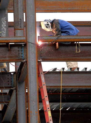 An ironworker works on the third residential-and-retail building at the Uptown project on Wednesday. Ari Maron, whose family is developing the project, said apartments in the first two buildings are 100 percent leased, with a waiting list of several hundred people. ABC the Tavern and Cleveland Yoga recently joined other restaurants and businesses at the project.