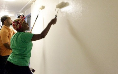 Thieann Rembert, right, and Juan Cedeno team up to paint a hallway in a public housing complex on Cleveland's East Side. Both hope their success in the Sherwin-Williams HomeWork Program leads to new jobs and careers.