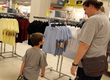 Soon-to-be-kindergartener Thomas Kerns, 5, gets an early glimpse of some Dockers school uniforms during a shopping trip with his mother, Leigh Ann Kerns, of Mayfield, at the Sears store in Richmond Heights. Experts say more parents are waiting for sales and holding off on buying all but the essentials as they shop for back to school on a budget.