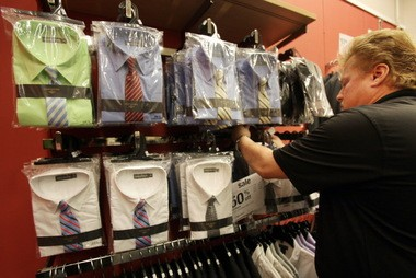 Store Manager David Suchka straightens shirt-and-tie combos for back-to-school at the Sears store in Richmond Town Square. More manufacturers are offering bundled sets to appeal to value-minded families.