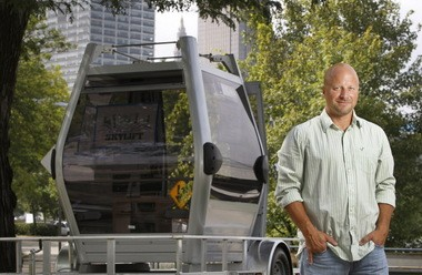 Jon Stahl, the president of LeanDog, stands next to a cable car he purchased and had shipped to Cleveland. The cable car, which sits on a strip of grass near LeanDog's floating offices, is one piece of an elaborate campaign Stahl has launched to bring a gondola system to the downtown lakefront.