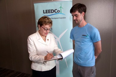 """U.S. Rep. Marcy Kaptur signs a """"power pledge"""" -- a promise to pay more for electricity generated by wind turbines - with LEEDCo employee Eric Ritter."""