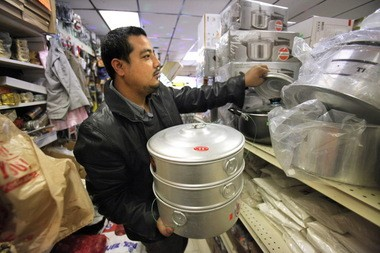 Nar Pradhan stocks cookware last week at the Lorain Avenue grocery he and his family opened to serve Cleveland's South Asian refugee community.