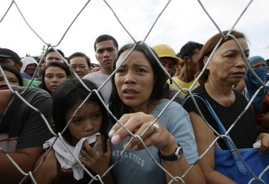 Residents line up for treatment and relief supplies Monday at Tacloban airport. Many survivors of the typhoon pleaded for food, water and medicine.