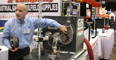 Tony Chirico, an exhibitor for Ray Lewis Company, a Youngstown industrial gas and oilfield supply company, shows how a display pump works to a customer at the Ohio Oil and Gas Exposition this week at the I-X Center. More than 200 exhibitors turned out for the two-day exposition.