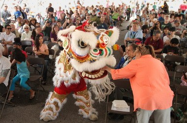 As is the custom, Victoria Meal of Brunswick feeds money to a roaring lion as the Kwan Family Lion Dance Team entertains at the Cleveland Asian Festival in May 2013.