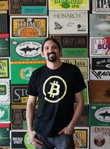 Nikhil Chand, founder of Bitcoin consultancy CoinNEO, stands in front of a craft beer display at The Wine Spot, which has been accepting virtual bitcoin payments for months.
