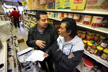 Nar Pradhan, left, whose family runs a grocery in the Bhutanese community of Cleveland, helps fellow refugee Moku Gurung understand the process of obtaining a green card.