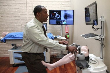 Mem David Sanders demonstrates a medical simulator at Simbionix offices in Cleveland in April. The company was sold this week to 3D System in South Carolina for $125 million cash.