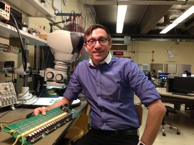 On a workbench at thinkbox, Ian Charnas holds a circuit board he uses to operate the Waterfall Swing.